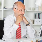 Confused businessman staring at computer at office desk Stock Photos