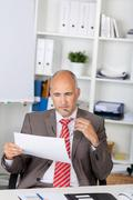 Businessman looking at document at desk Stock Photos
