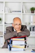 Businessman leaning with folded arms on binders Stock Photos