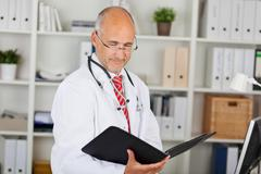 Doctor reading folder against shelves in office Stock Photos