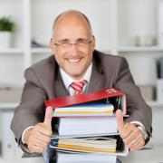 businessman with stack of books gesturing thumbs up - stock photo