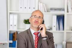 Businessman puckering lips while using cordless phone Stock Photos