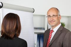 businesspeople standing by flipchart - stock photo