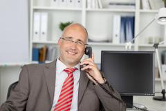 Relaxed businessman calling by phone Stock Photos