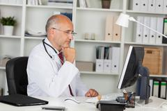 doctor working with computer - stock photo