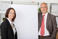 two colleagues standing next to white flipchart - stock photo