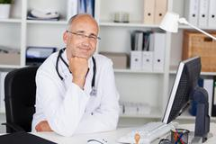 Smiling doctor with chin on hand Stock Photos