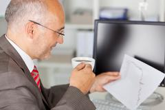 Businessman analyzing line graph while holding coffee cup Stock Photos