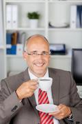 Happy mature businessman having coffee Stock Photos