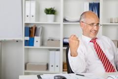 Businessman with clenched fist celebrating victory at desk Stock Photos