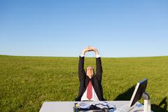 businessman stretching at desk on grassy field against sky - stock photo