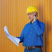 architect holding blueprints while using mobile phone - stock photo