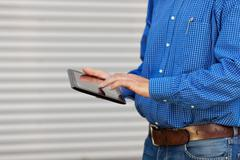 midsection of architect using digital tablet - stock photo