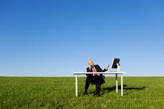 man using landline phone at desk on field against sky - stock photo