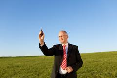 businessman writing on invisible screen with marker on field - stock photo