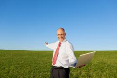 Excited businessman with arms outstretched holding laptop on fil Stock Photos