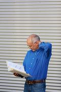 Stock Photo of confused businessman reading binder against shutter