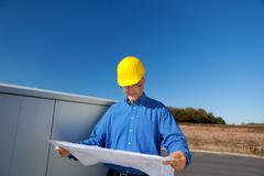 Architect examining blueprint against clear sky Stock Photos