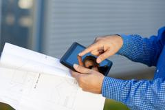 architect's hands holding blueprint while using digital tablet - stock photo