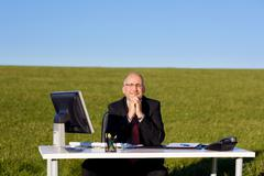 businessman with hands clasped sitting at desk on field - stock photo