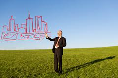 Mature businessman drawing buildings in field Stock Photos