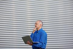 thoughtful businessman with laptop while looking away - stock photo