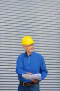 architect holding blueprint while looking away - stock photo