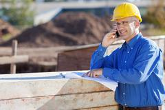 architect pointing at blueprint while using mobile phone at site - stock photo