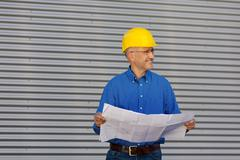 Stock Photo of architect holding blueprint while looking away against shutter