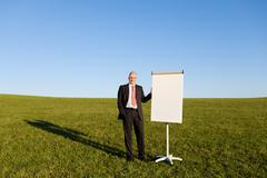 Mature businessman by blank flipchart on grassy field Stock Photos