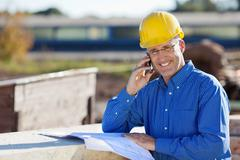 smiling architect using mobile phone at site - stock photo