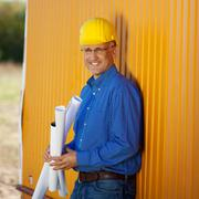 confident architect holding blueprints while leaning on trailer - stock photo