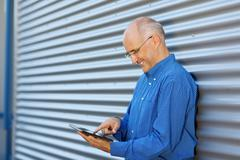 Stock Photo of businessman using digital tablet against shutter