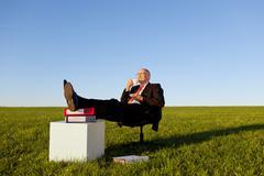 Businessman enjoying coffee on chair in grassy field against sky Stock Photos
