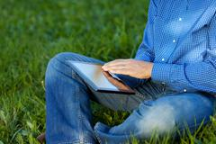 Midsection of businessman using digital tablet on grass Stock Photos