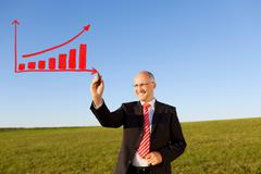 Businessman drawing bar graph on field against sky Stock Photos