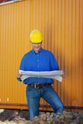 architect wearing hardhat while examining blue print - stock photo