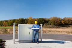 architect holding blueprint while standing against electric box - stock photo