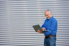 Businessman holding laptop outdoor Stock Photos