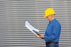 architect holding digital tablet while looking at blueprint agai - stock photo