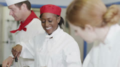 Happy team of chefs in commercial kitchen, preparing food and chatting together - stock footage