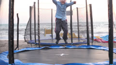 Boy jumping on a trampoline beach   2 Stock Footage