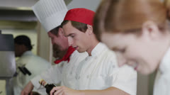 Happy team of chefs in commercial kitchen, preparing food and chatting together Stock Footage