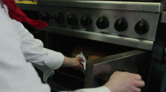 Mature male chef takes a tray of freshly baked bread out of the oven - stock footage