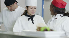 Happy team of chefs in a commercial kitchen, head chef gives instructions Stock Footage
