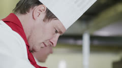 Professional chef in a commercial kitchen concentrating on his work Stock Footage