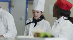 Happy team of chefs in a commercial kitchen, head chef tastes and gives approval - stock footage