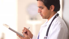 Hispanic doctor working on medical chart Stock Footage
