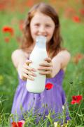 Girl holding a bottle of fresh milk Stock Photos