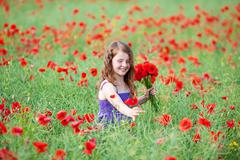 beautiful little girl picking red poppies - stock photo